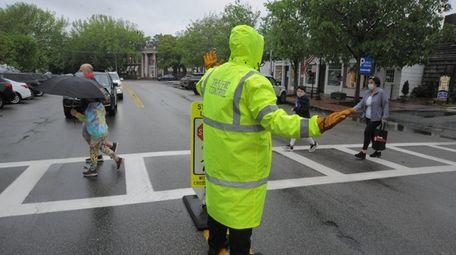 People cross the street on Main Street in