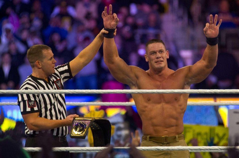 John Cena celebrates his victory over The Rock