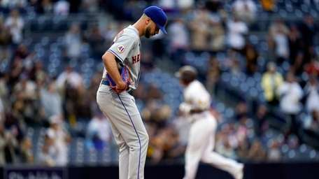 Mets starting pitcher Joey Lucchesi, left, cleans off
