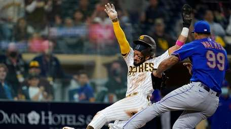 Fernando Tatis Jr. of the Padres scores from third place