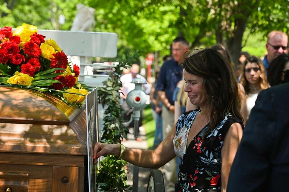Friends and family place flowers the horse-drawn carriage