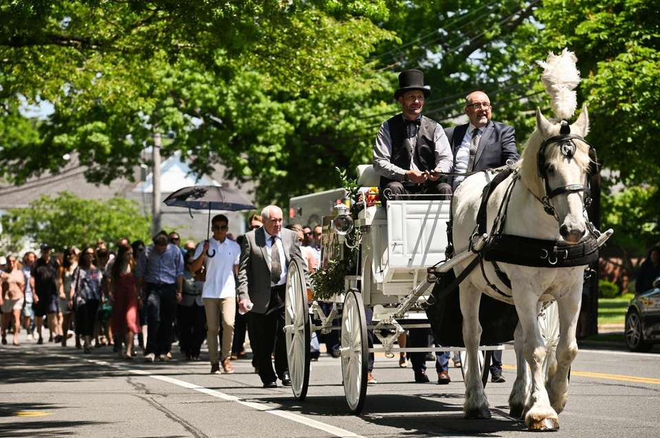 A crowd walks behind the horse-drawn carriage carrying
