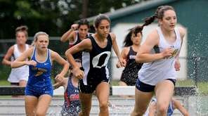 Runners compete in the girls 2000 meter steeplechase,