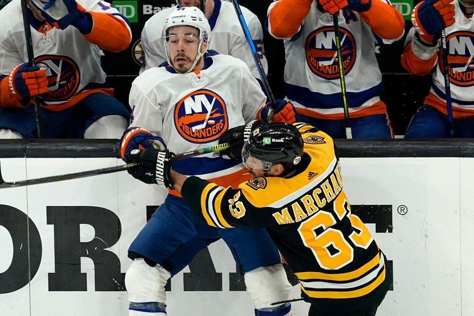 Boston Bruins center Brad Marchand (63) checks New