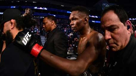 Israel Adesanya is escorted out of the ring