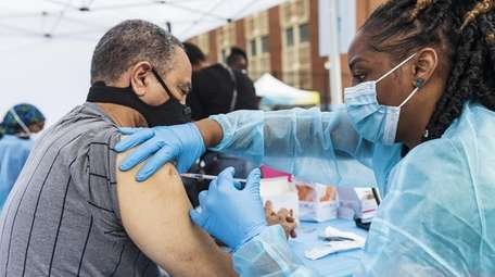 Registered nurse Sheba Phillip administers a COVID-19 vaccine