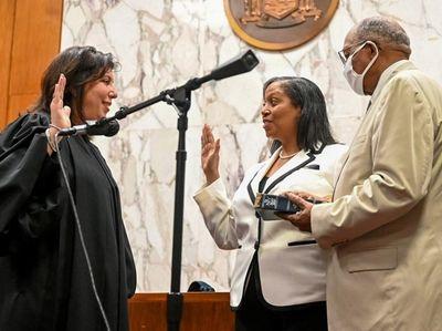 Joyce A. Smith, middle, is sworn in as