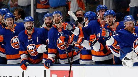 The Islanders bench celebrates an empty net goal