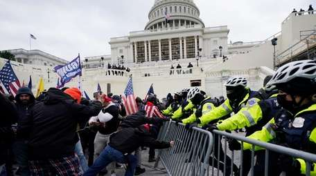 Trump supporters work to breach a police barrier