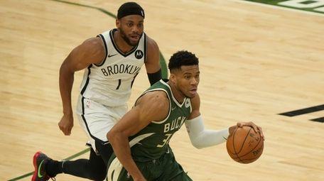 The Bucks' Giannis Antetokounmpo drives past the Nets'