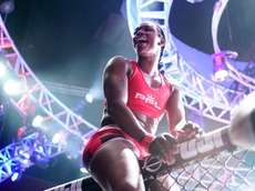 Claressa Shields climbs the cage after a Professional