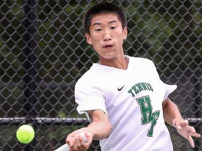 Chris Qi of Harborfields returns service at the