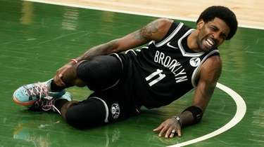 The Nets' Kyrie Irving holds his leg after