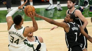 The Bucks' Giannis Antetokounmpo shoots over the Nets'