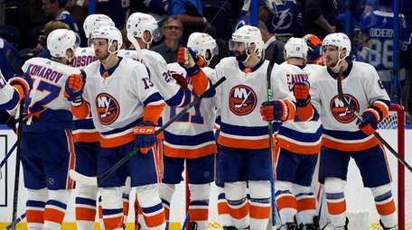 Islanders players celebrate after defeating the Lightning in