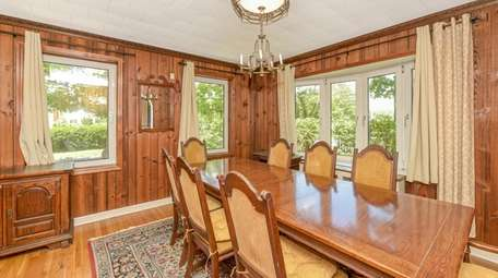 The house has a formal, wood-paneled dining room.
