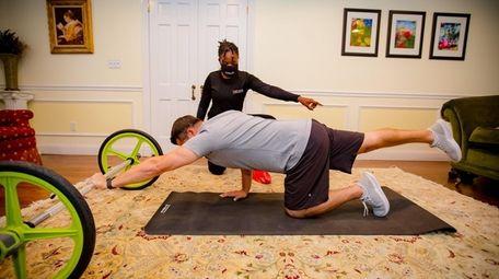 A GYMGUYZ trainer guides a client a workout