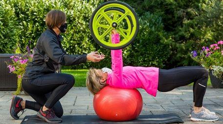 A GYMGUYZ trainer gives a client an outdoor