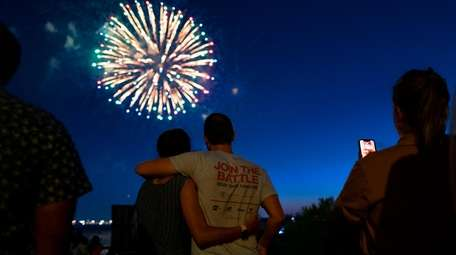 A couple hugs as they watch fireworks over