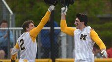 Robert Stang #23, Massapequa catcher, right, gets congratulated