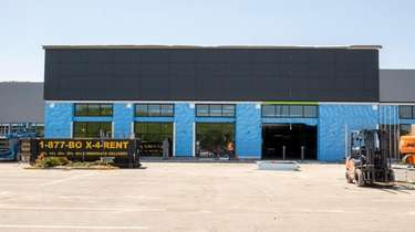 Construction workers build an Amazon Fresh opening at
