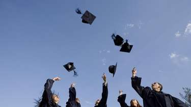 Graduates throwing graduation caps into air.