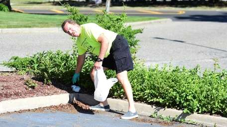 Mel Silverman picks up discarded items along Route