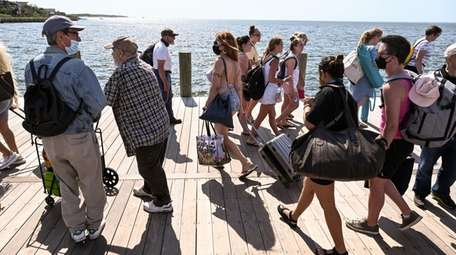 People walk to and from the Sayville Ferry