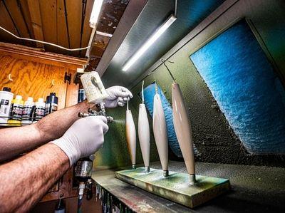 Chris Voorhies paints the plugs in his workshop