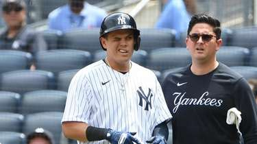 A trainer checks on Yankees' Gio Urshela after