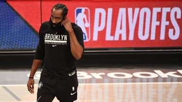 Nets guard James Harden looks on while warming