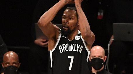 Nets forward Kevin Durant shoots over Bucks forward