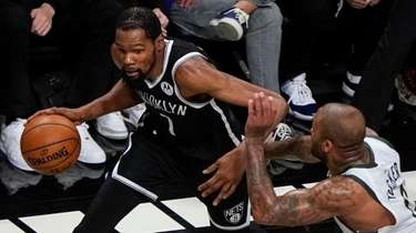 The Nets' Kevin Durant, left, drives past the
