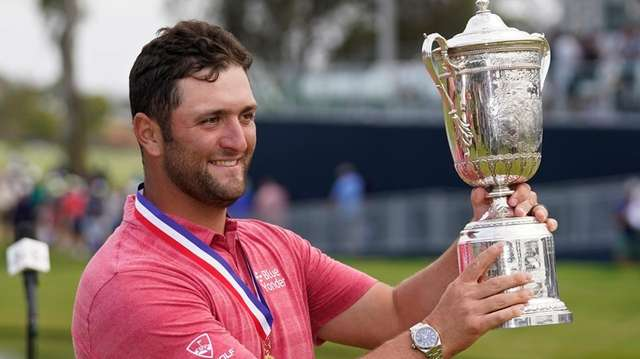 Jon Rahm holds the champions trophy after the