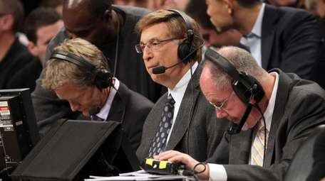 Broadcaster Marv Albert works the game between the