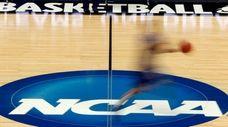 A player runs across the NCAA logo during