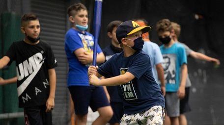 Logan Mann, 9, of Merrick, plays wiffle ball
