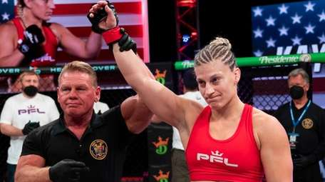Kayla Harrison has her hand raised in victory