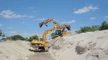Heavy equipment is being used to move sand