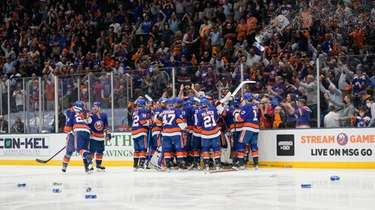Fans cheer as the Islanders celebrates after Game