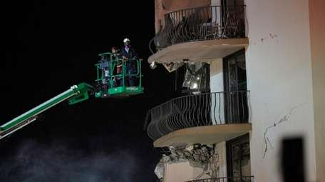 Workers use a lift to investigate balconies in