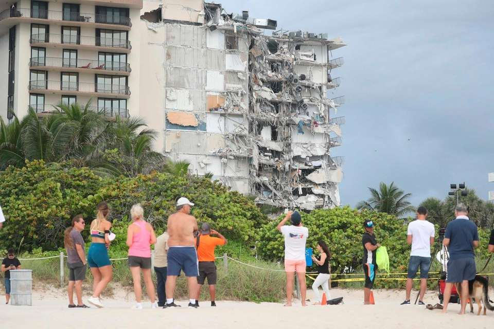 People look at the damage at the 12-story