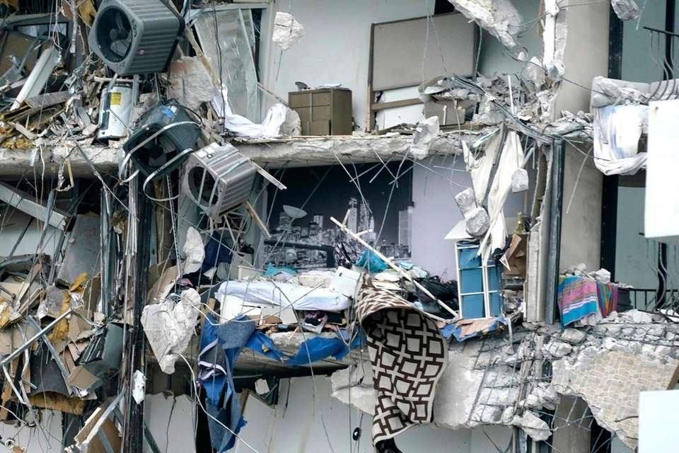 Household items and debris dangle from a partially