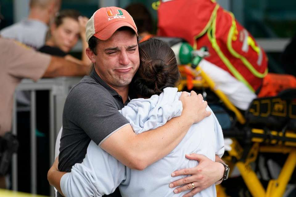 A couple embrace as they wait for news