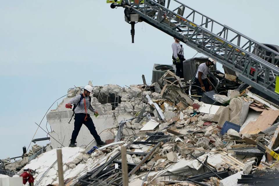 Rescue worker walk among the rubble where a