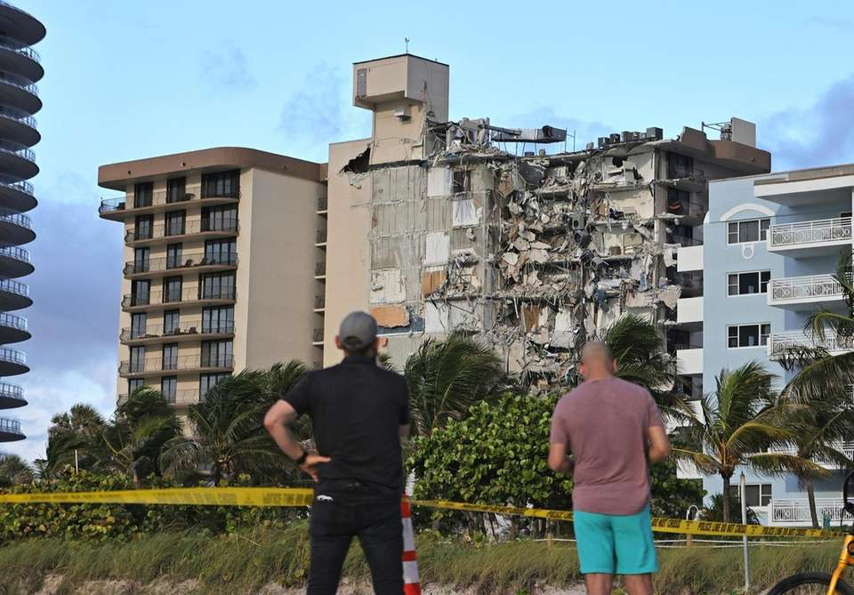 People look at the partially collapsed Champlain Towers