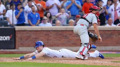 Billy McKinney #60 of the Mets dives across