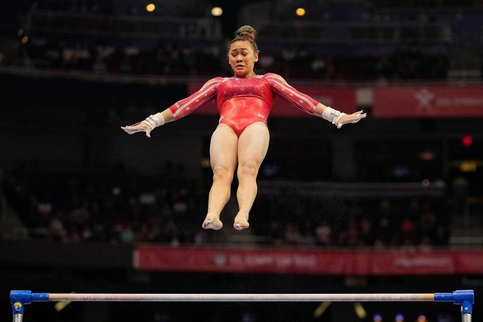 Suni Lee competes on the uneven bars during