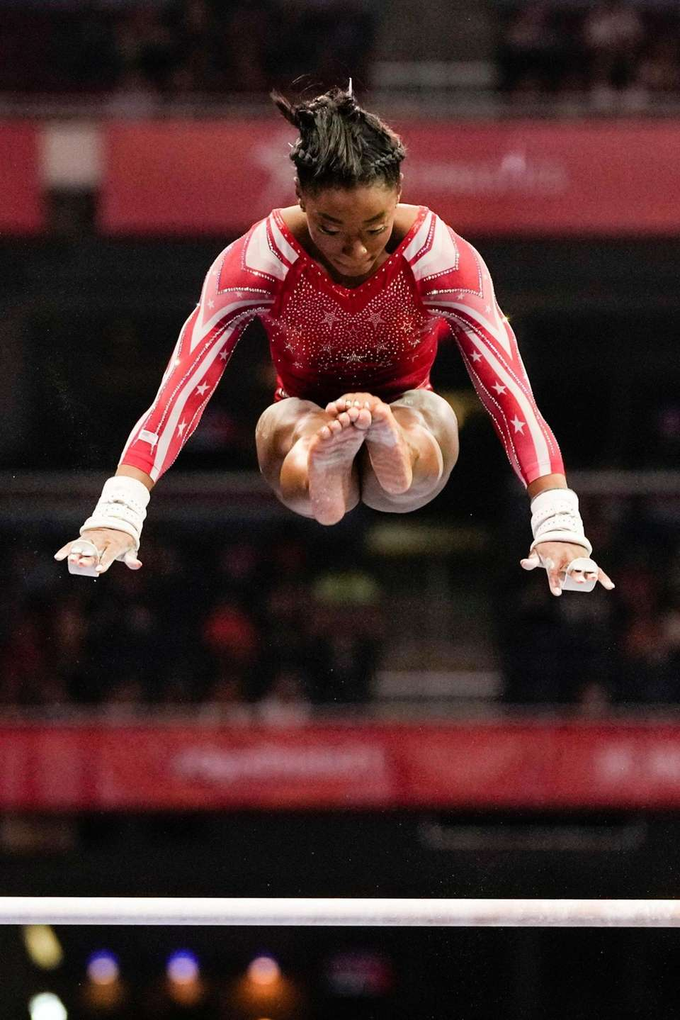 Simone Biles competes on the uneven bars during