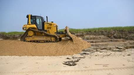 A bulldozer replaces sand lost to erosion at